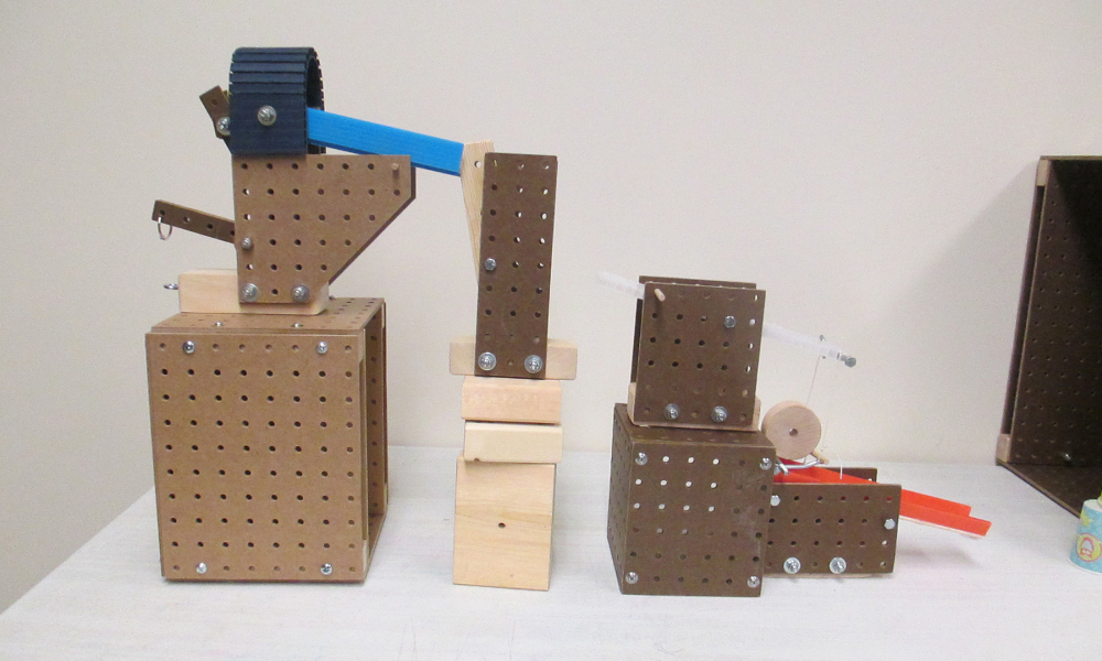 Use a variety of blocks, balls, ramps, string, and other materials.