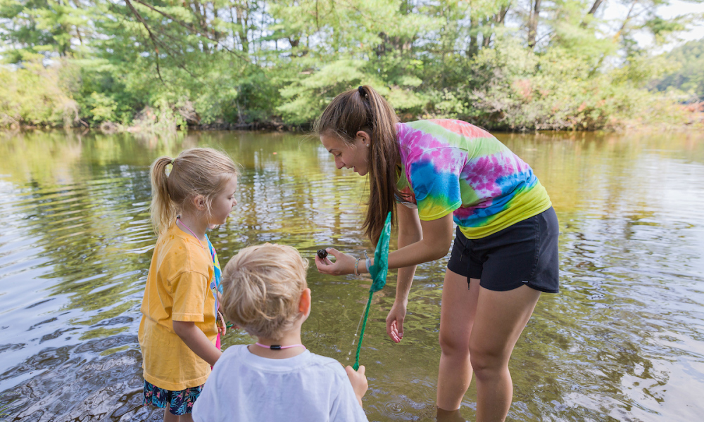 Summer camp educators teach campers while exploring the world around